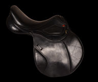 Black leather premium jumping saddle isolated at black backgroun Stock Image