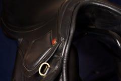 Black leather professional jumping  saddle  at black background Royalty Free Stock Photos