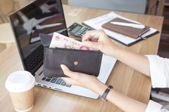 Black leather purse with hundred Chinese yuan banknote in young. Woman hands at the office. Top view Stock Photos