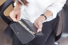 Black leather purse with hundred dollar banknote in young woman. Hands. Top view Stock Photography