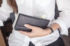 Black leather purse with hundred dollar banknote in young woman. Hands. Top view Stock Photo