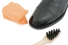Black leather shoe with rag and brush Stock Photo
