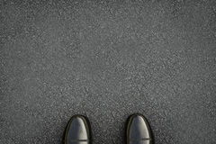 Black leather shoes on asphalt road Royalty Free Stock Photos