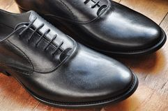Black Leather Shoes on Brown Wooden Tile Floor Royalty Free Stock Image