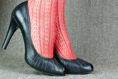 Black leather shoes with red tights Stock Photos