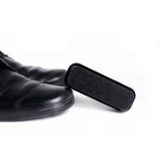 Black leather shoes and sponge Royalty Free Stock Photography