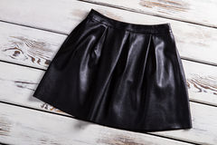 Black leather skirt with folds. Leather skirt on wooden background. Merchandise at a nice discount. New clothes from city shop Stock Photo