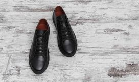 Black leather sneakers on a light laminate. Place to place your text royalty free stock photography