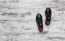 Black leather sneakers on a light laminate. Place to place your text royalty free stock photo