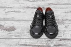 Black leather sneakers on a light laminate. Place to place your text stock photos