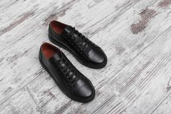 Black leather sneakers on a light laminate. Place to place your text stock photography