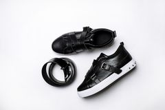 Black leather sneakers with straps and white sole and leather black belt on a white background royalty free stock photo