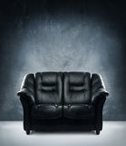 A black leather sofa on a dark grunge background Stock Photo