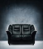 A black leather sofa on a dark grunge background Stock Photo