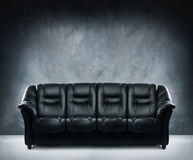 Black leather sofa in dramatic interior Royalty Free Stock Photo