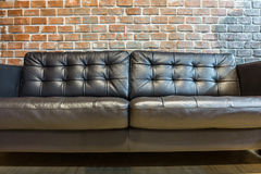 Black leather sofa for interior design in a room. The sofa and brick wall Royalty Free Stock Photos