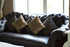 Black leather sofa in luxurious interior room. Selective focus Stock Image