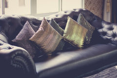 Black leather sofa in luxurious interior room. Vintage filter,selective focus Royalty Free Stock Photos