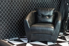 Black leather sofa. It is in studio room Royalty Free Stock Images