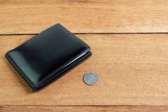 Black leather wallet with 5 baht coins on wooden floor royalty free stock images