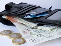 Wallet containing several ten pound notes with pound coins. A black leather wallet containing credit and debit cards and paper currency with three pound coins in Royalty Free Stock Photos