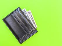 Black leather wallet with dollar bills on a green background. stock photos