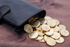 Black leather wallet with golden coins on wood background Royalty Free Stock Photos