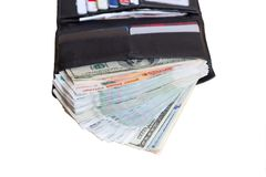 Black leather wallet with lots of cash, rubles and dollars. Rich in purse on white background lies open, blurry plastic cards in the background Royalty Free Stock Photos