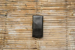 Black leather wallet. Placed on a table, bamboo is old Bill paid for the goods, or buying used Royalty Free Stock Image