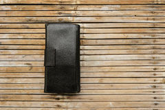 Black leather wallet. Placed on a table, bamboo is old Bill paid for the goods, or buying used Royalty Free Stock Images