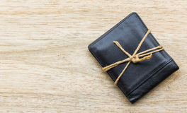 Black leather wallet with ropes on wood background. Stock Photo