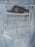 Black leather wallet sticking in the back pocket of denim  jeans Stock Image