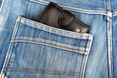 Black leather wallet sticking in the back pocket of  jeans Royalty Free Stock Photography