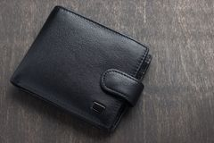 Black leather wallet on a wooden background.  royalty free stock photos