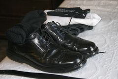 Black leather wingtip mens dress shoes with black socks and belt. Black leather wingtip men`s dress shoes with black socks and belt. Hanky, shoes, and Stock Image