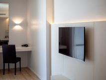 Black LED television on white wall near makeup corner with black chair in hotel room. Black LED television on white wall near makeup corner with black chair in royalty free stock images