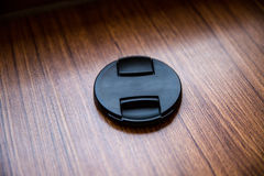 Black lens cap. On wooden background Royalty Free Stock Photos