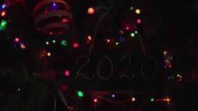 2020 lettering chalkboard hanging on a branch is Christmas tree. Black letter board with number 2020 on it hanging on a branch is Christmas tree among glass stock video