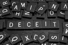 Black letter tiles spelling the word & x22;deceit& x22;. On a reflective background stock images