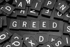 Black letter tiles spelling the word & x22;greed& x22;. On a reflective background stock images