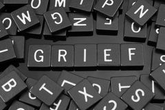 Black letter tiles spelling the word & x22;grief& x22;. On a reflective background Stock Photo