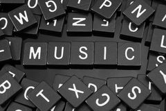 Black letter tiles spelling the word & x22;music& x22;. On a reflective background Stock Photos