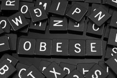 Black letter tiles spelling the word & x22;obese& x22;. Black letter tiles spelling the word & x22;obese& x22; on a reflective background Stock Image