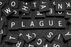 Black letter tiles spelling the word & x22;plague& x22; Royalty Free Stock Images