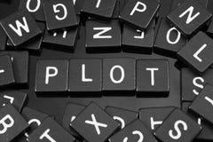 Black letter tiles spelling the word & x22;plot& x22; Royalty Free Stock Image
