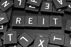 Black letter tiles spelling the word & x22;REIT& x22;. On a reflective background Stock Image