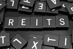 Black letter tiles spelling the word & x22;REITs& x22; stock images