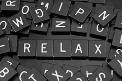 Black letter tiles spelling the word & x22;relax& x22;. On a reflective background Stock Photo