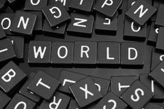 Black letter tiles spelling the word & x22;world& x22;. On a reflective background Stock Photos