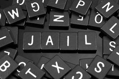 Black letter tiles spelling the word & x22;jail& x22; Royalty Free Stock Photo
